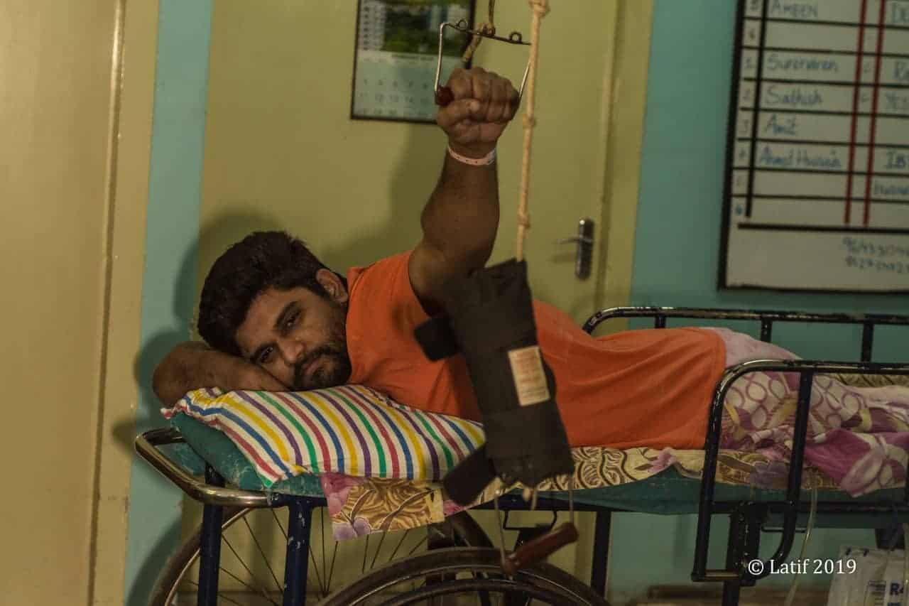 spinal cord injured man lying on his stomach on a prone trolley in rehab